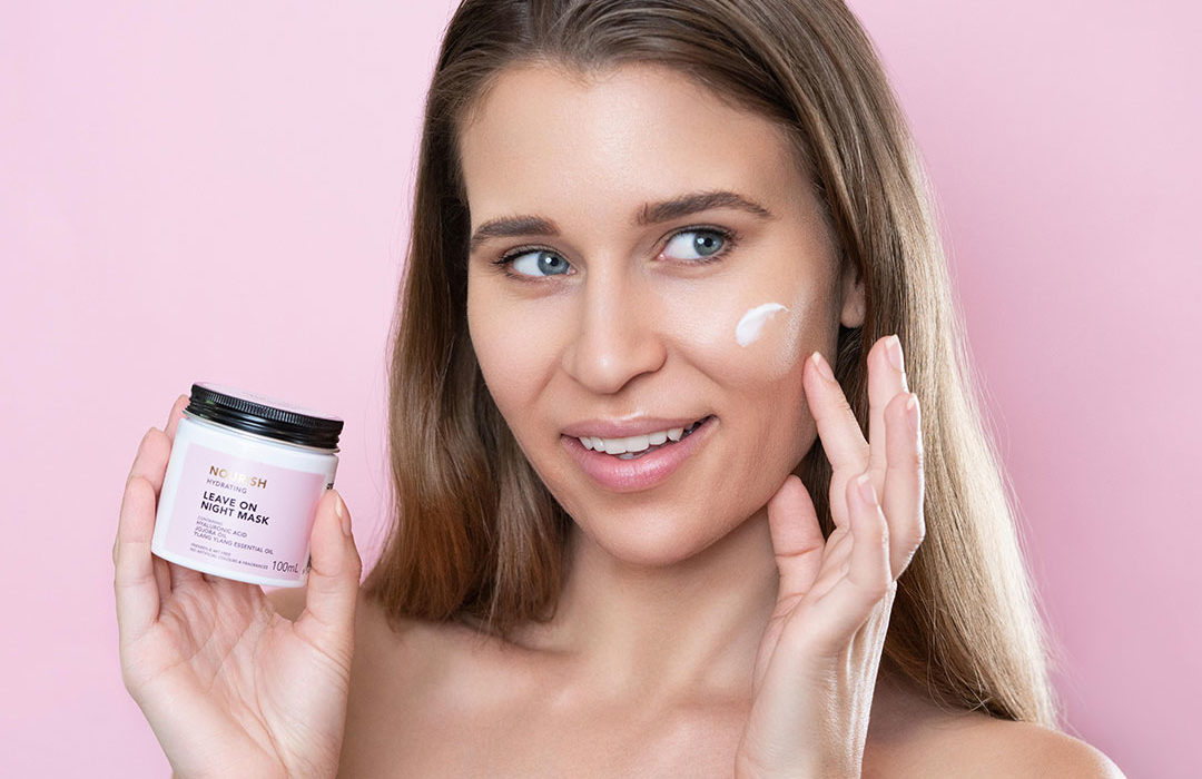amy rose hancock woman holding skincare product on pink background